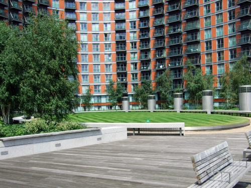 Courtyard with lawn, walkways and benches surrounded by high residential buildings